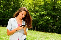 Teenage girl using mobile phone while walking in countryside
