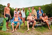 Teenagers chilling out together in swimming clothes in countryside