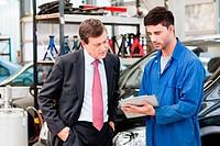 Businessman with car mechanics in repair garage