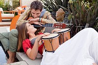 Couple with musical instrument resting on bench