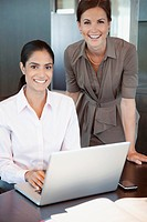 Two women in office working with laptop