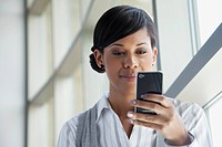 Portrait of young businesswoman texting on cell phone