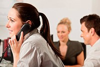 Female employee using a telephone in the office