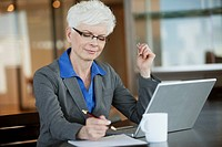 Businesswoman working at desk (thumbnail)