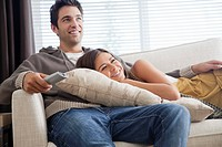 Couple relaxing on sofa and watching tv