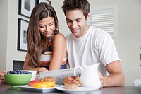 Young couple having breakfast and reading newspaper (thumbnail)