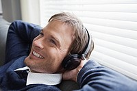 Young smiling man listening music