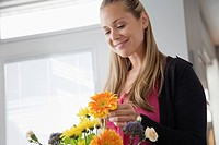 Young woman arranging flower bouquet
