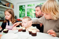 Mid adult man and family decorating cupcakes