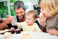 Mid adult man decorating cupcakes with his sons