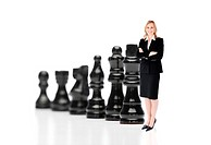 Businesswoman in front of black chess pieces on white background