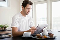 Man reading newspaper during breakfast