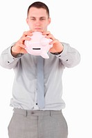 Portrait of a businessman shaking a piggy bank against a white background
