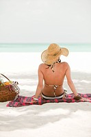 Woman in Bikini and Floppy Hat Sitting on Beach Blanket, Rear View, Aruba