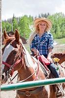 Blonde Girl Riding Horse in Enclosed Pen