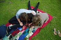 Teenagers using digital tablet in park