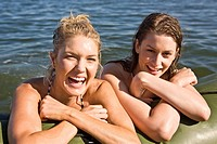 Two Smiling Young Women in Water Resting on Side of Dinghy