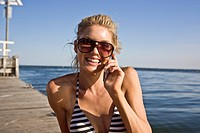 Smiling Young Woman Sunbathing and Talking on Cell Phone on Pier