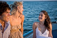 Two Young Women and Young Man Relaxing on Boat