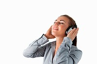 Businesswoman listening to music against a white background