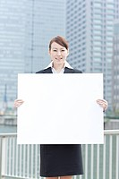 Young businesswoman holding a blank board
