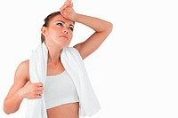 Sporty female wiping sweat off her forehead against a white background