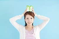 Young Woman Holding Gift On Top Of Her Head
