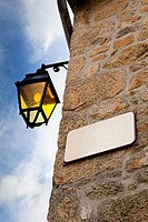 Corner of old stone building with wall lamp and blank street name sign, low angle view