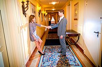 Couple holding hands in a hotel corridor