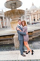 Couple standing in front of a water fountain in Saint Peter's square Rome Italy