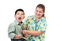 A young boy reacts to the cold stethoscope as the nurse checks the heart beat