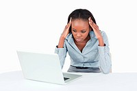 Tired businesswoman working with a laptop against a white background