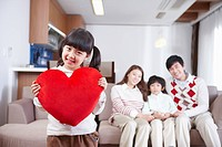 Happy family and a girl holding a red heart cushion