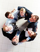 Above view of several business partners looking upwards at camera while embracing each other