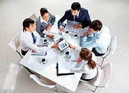 Above view of business team sitting around table and working with papers
