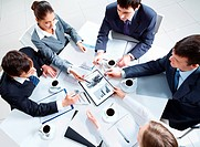 Above view of business team discussing papers at meeting