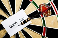 Dart on bulls eye target of dartboard