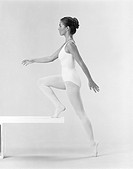 Young woman in leotard leaning against balance beam
