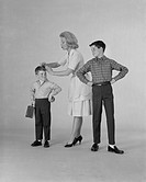 Mother dressing up two sons on white background