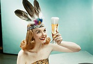 Young woman wearing feather headdress, holding beer glass