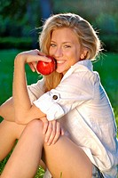 Attractive young blonde woman in nature, holding a fresh apple