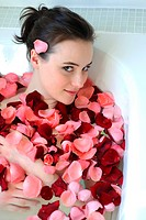 Young woman enjoying bath with rose petals