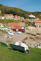 Couple sitting on bench overlooking sea at Runswick Bay village near Whitby on the North Yorkshire coast, England, United Kingdom