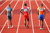 3 Young Male Athletes Walking Back to Start Blocks in Men´s 100 Meters Training