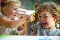Little girl wiping paint on her brother´s nose