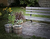 A weathered wood bench and three weathered wood planters with flowers and plants in a peacefull outdoor garden in the city