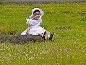 Small girl seating at green heaths, Plateau of flowers, Kaas, Satara, Maharashtra, India