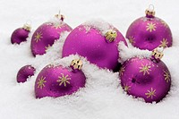 digital enhancement - arrangement of christmas tree baubles on snow - shop window advertising