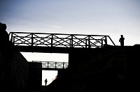 Two seperate people standing, and footbridges, silhouetted at dusk, UK