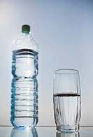 glass of fresh drinking water with plastic bottle